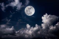与明亮的满月的夜空和多云,平静自然后面 免版税图库摄影