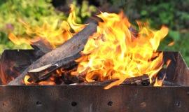 与明亮的火焰的热的木炭烤肉格栅在自然后面 图库摄影