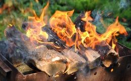 与明亮的火焰的热的木炭烤肉格栅在自然 免版税库存图片