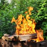 与明亮的火焰的热的木炭烤肉格栅 免版税库存照片