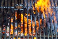 与明亮的火焰的空的热的木炭烤肉格栅 库存图片