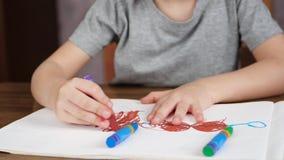 与明亮的色的铅笔的未知的儿童图画在白皮书,当坐在桌上时 发展的概念 股票视频