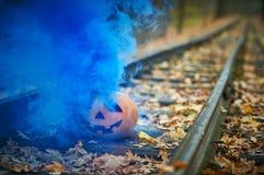 与明亮的蓝色烟的微笑的万圣夜南瓜在路轨在森林里 库存图片
