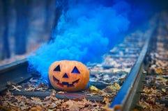 与明亮的蓝色烟的微笑的万圣夜南瓜在路轨在森林里 库存照片