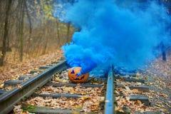 与明亮的蓝色烟的微笑的万圣夜南瓜在路轨在森林里 免版税库存图片