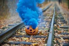 与明亮的蓝色烟的微笑的万圣夜南瓜在路轨在森林里 免版税图库摄影