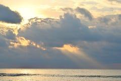 与明亮,金黄黄色和橙色气氛的太阳,在落在风平浪静水的乌云和阳光后通过在天空的云彩 图库摄影