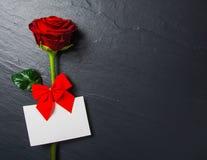 与明信片的红色玫瑰在石背景 免版税库存图片