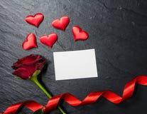与明信片的红色玫瑰在石背景 库存图片