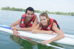 与明轮轮叶的年轻夫妇游泳在湖 库存照片