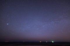 与星的夜空在海滩 蓝色展望期少校编号安排了行星空间范围视图 库存图片