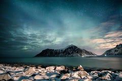 与星的极光borealis在与多雪的海岸线的山脉在Skagsanden海滩 免版税库存照片