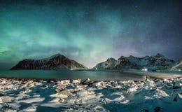与星的极光borealis在与多雪的海岸线的山脉在Skagsanden海滩 免版税图库摄影