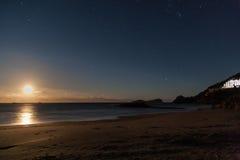 与星的被月光照亮海滩在夜空 免版税库存图片