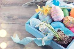 与春天花的复活节五颜六色的被绘的鸡蛋和在木头的蓝色缎丝带 库存照片
