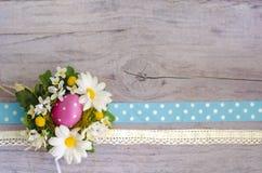 与春黄菊、复活节彩蛋和被察觉的丝带的木织地不很细表面 您的设计的美好的模板 库存图片