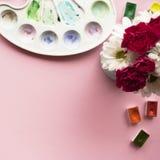 与春黄菊和康乃馨,水彩,在桃红色背景的调色板花束的艺术家工作区与您的文本的地方 f 免版税库存照片