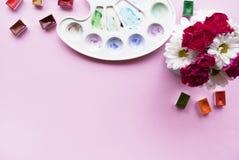 与春黄菊和康乃馨,水彩,在桃红色背景的调色板花束的艺术家工作区与您的文本的地方 f 免版税库存图片
