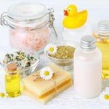 与春黄菊油、花、肥皂、盐和有机化妆用品,正方形的婴孩浴 免版税库存照片