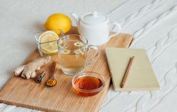 与春黄菊花、姜黄和蜂蜜的清凉茶在一个木板 热的饮料姜的治疗 民间补救 库存图片