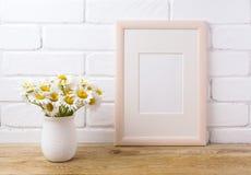 与春黄菊花束的木制框架大模型在土气花瓶 库存照片