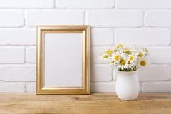 与春黄菊花束的金黄框架大模型在土气花瓶 免版税图库摄影