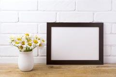 与春黄菊花束的黑棕色风景框架大模型在ru 库存照片
