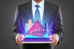 与显示发光的图表三角形状的片剂个人计算机的商人 库存照片