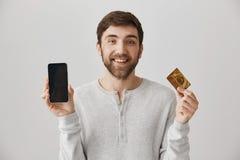 与显示智能手机和信用卡的逗人喜爱的微笑的正面欧洲男性模型在照相机,站立在灰色背景 免版税图库摄影