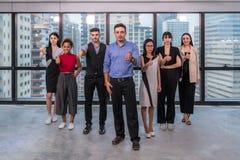 与显示赞许的雇员小组的商业领袖看照相机,愉快的专业多文化办公室队人民 库存图片