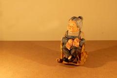 与晃动与蜡烛的光的可爱的资深夫妇玩偶选址的静物画摄影竹椅子在黑暗的在木头bac 图库摄影