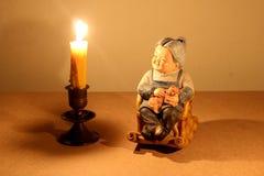与晃动与蜡烛的光的可爱的资深夫妇玩偶选址的静物画摄影竹椅子在黑暗的在木头bac 免版税库存图片
