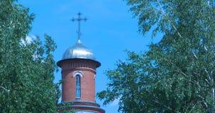 与晴朗的光芒,在前景的开花的绿色树的正统寺庙桔子砖 蓝色覆盖天空白色 祈祷,圣洁 图库摄影