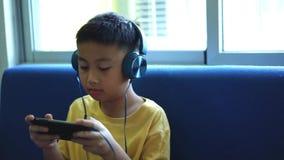 与智能手机和佩带的耳机的愉快的孩子戏剧比赛在家 股票视频