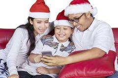 与智能手机和圣诞老人帽子的亚洲家庭 免版税库存照片