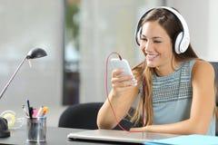 与智能手机和耳机的女孩听的音乐 免版税图库摄影