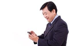 与智能手机应用的愉快的商人 免版税图库摄影