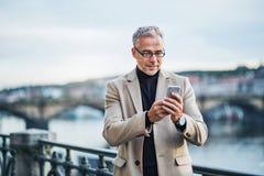 与智能手机支持的河的成熟商人在布拉格市,采取selfie 免版税图库摄影