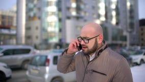 与智能手机横穿城市街道的年轻商人 年轻人沿着走有电话的街道 人讲话  影视素材