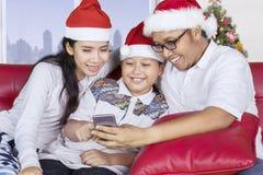 与智能手机的亚洲家庭在圣诞节时间 免版税库存照片