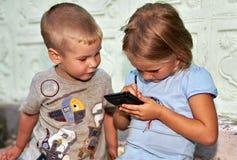 与智能手机的儿童游戏 免版税库存图片