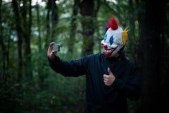 与智能手机的可怕小丑作为selfie在木头 图库摄影