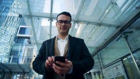 与智能手机的可爱的商人在企业摩天大楼附近站立 影视素材