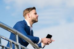 与智能手机的商人在蓝天,营业通讯的大阳台 免版税库存照片