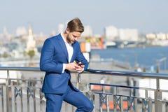 与智能手机的商人在都市风景,营业通讯的大阳台 库存图片