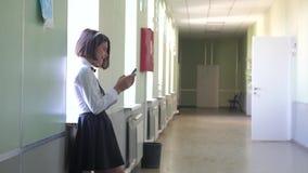 与智能手机的女小学生教育在学校概念 少女青少年和生活方式使用智能手机待命 影视素材