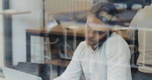 与智能手机的年轻商人写下企业信息的在他的笔记薄,当看在玻璃状时的膝上型计算机 股票视频