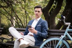 与智能手机的年轻商人坐一条长凳在公园 库存照片