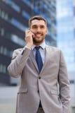 与智能手机的微笑的商人户外 免版税库存图片
