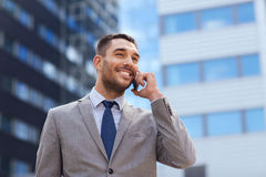与智能手机的微笑的商人户外 库存照片